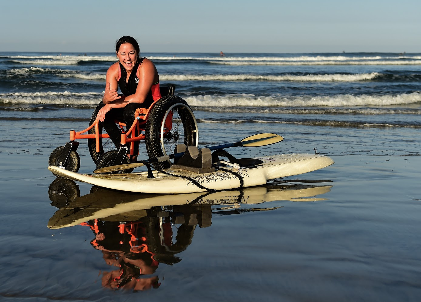 Alana sitting in wheelchair at beach with adaptive surfboard at her feet.