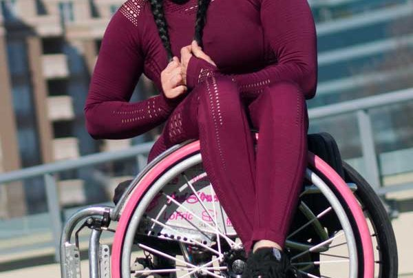 Paraplegic women sitting in a wheelchair with legs straddled over the side
