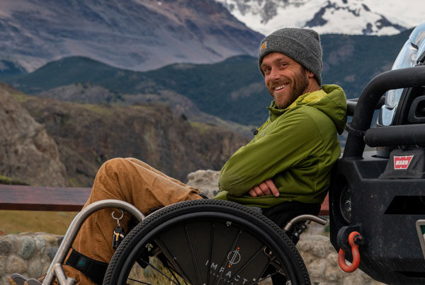 Kirk Williams leaning back in his wheelchair against his van with the mountians of Patagonia in the background.